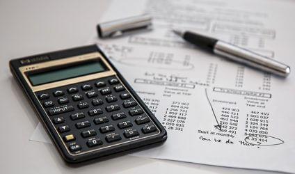 Ein Haushaltsbuch mit Taschenrechner und Stift führen